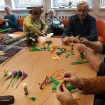 Seniorzy przygotowują kwiaty z krepiny